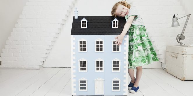 Happy girl leaning against doll house in attic loft