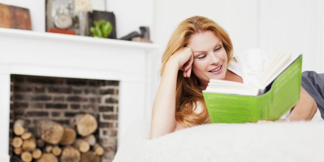 Woman lying on bed in front of brick-built fireplace reading a book