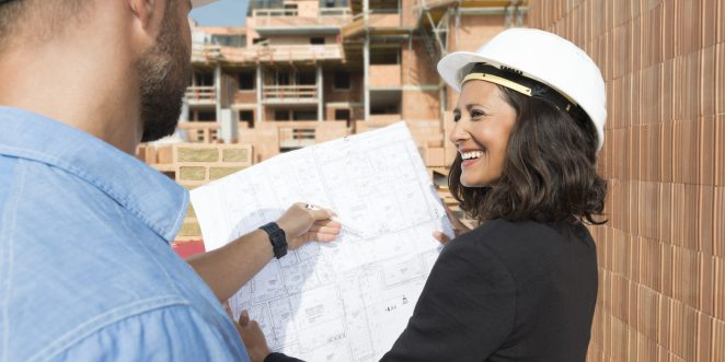 Male and female Architect with technical drawing on construction site