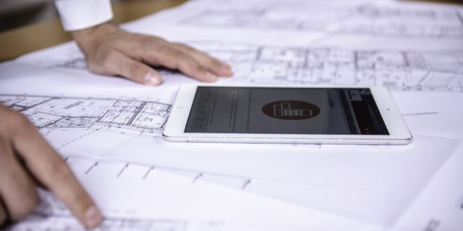 Tablet computer and hands at blueprint
