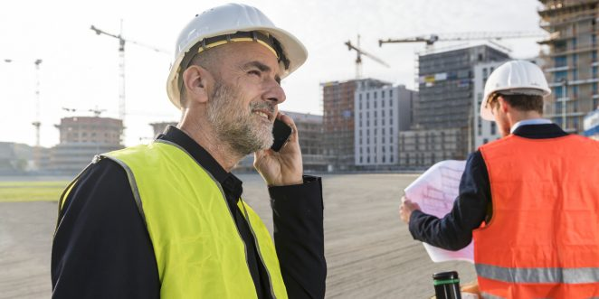 Architect on the phone while his colleague is looking at a plueprint, unfinished buildings in the background, Fast Forward Commercial Excellence